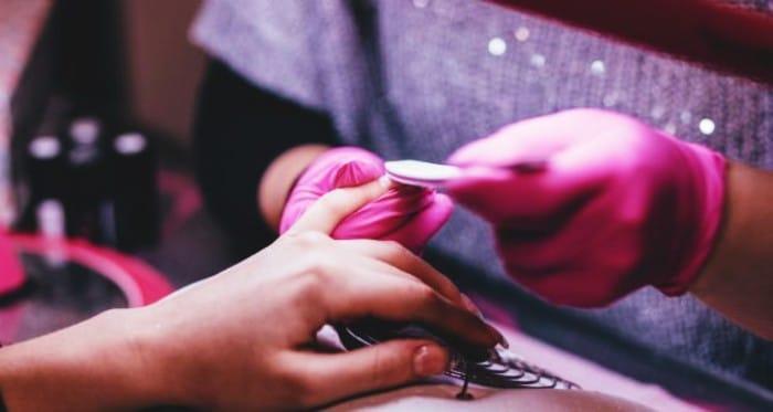 El uso de guantes como medida de seguridad al aplicar uñas acrílicas
